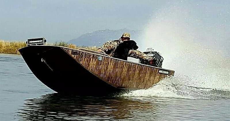 widowmaker 2048 hybrid V mud boat with camo wrap and a black labrador cruising through the water